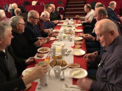 Ett fyrtiotal personer längs ett långt bord, alla äter gröt.