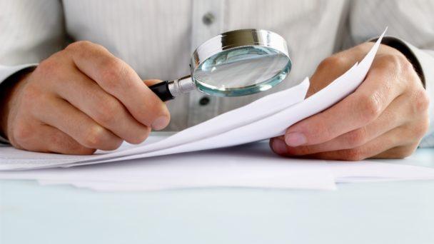 En person tittar på ett papper genom ett förstoringsglas