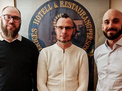 Gruppbild: Mikael Andersson, Patric Nelson och Sebastian Brandt med HRF:s emblem i bakgrunden