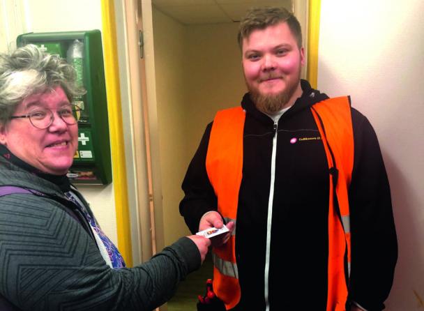 Ninni Blom överräcker ett papper till en person i orange väst