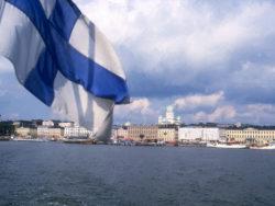 Helsingfors skyline, vatten och den finska flaggan