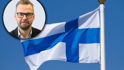 Den finska flaggan med en porträttbild av Jari Ollila monterad över