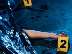 En hand som sticker ut under et plastskynke på ett golv på en brottsplats.