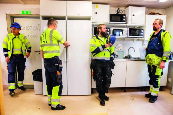 Fyra personer i arbetskläder i ett personalkök