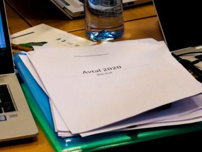 En bunt papper på ett mötesbord, med texten Avtal 2020 på omslaget