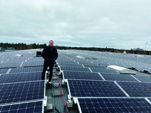 Rickard Lantz på ett tak bland solpaneler.