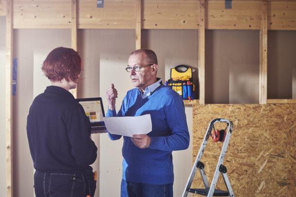 Två personer pratar på en byggarbetsplats