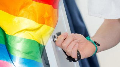 Handen på en person som låter upp ett skåp i ett omklädningsrum, noterat invid en prideflagga