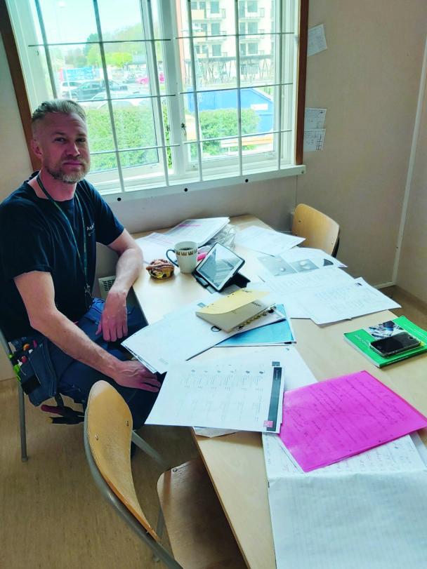 Tomas vid ett bord med papper på