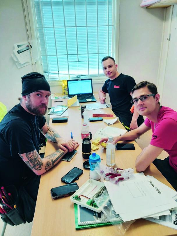 Tre personer vid ett bord med papper på