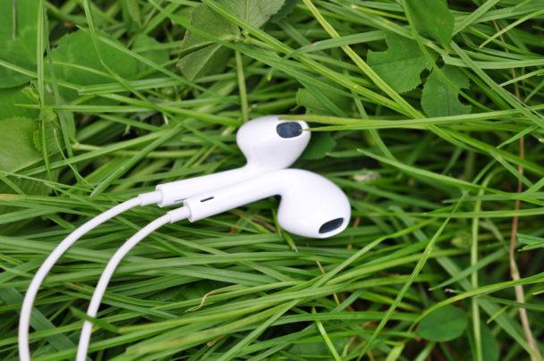 Ett par hörlurar som ligger i grönt gräs