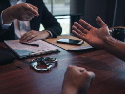 En person pekar anklagande på en annan person över ett skrivbord med handklovar på.