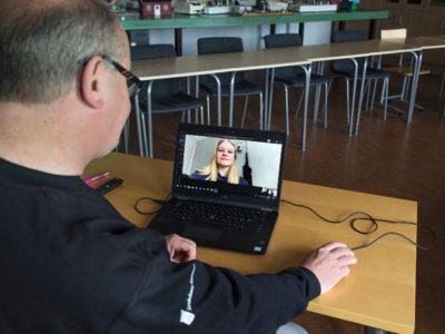 Läraren framför sin laptop, med en videochat med en elev på skärmen