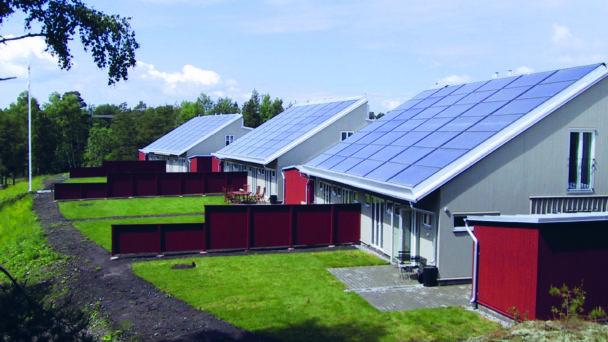 En rad hus med solpaneler på taken
