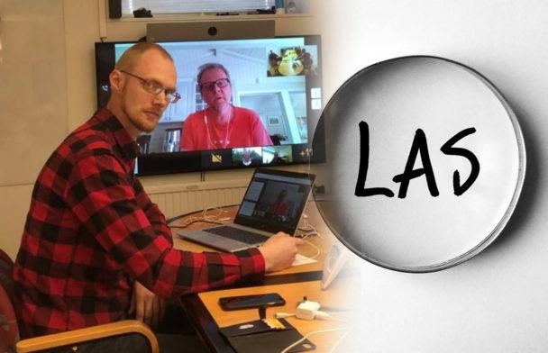 David Aura framför en dator med Urban Pettersson på skärmen. En bild på ett förstoringsglas som är riktat mot ordet LAS är monterad invid.