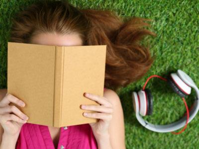 En person logger I gräset och läser en bok, med ett par hörlurar bredvid sig