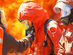 Personer i brandskyddskläder framför en skogsbrand