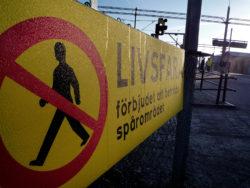"""En varningsskylt med en överstruken fotgängare, och texten """"Förbjudet att beträda spårområdet"""""""