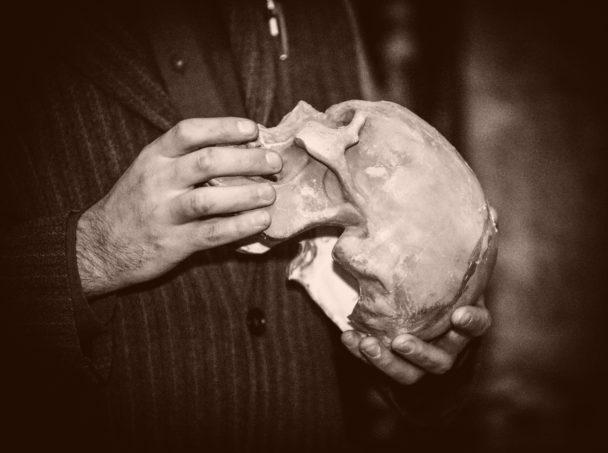 Händerna på en person som håller i en dödskalle