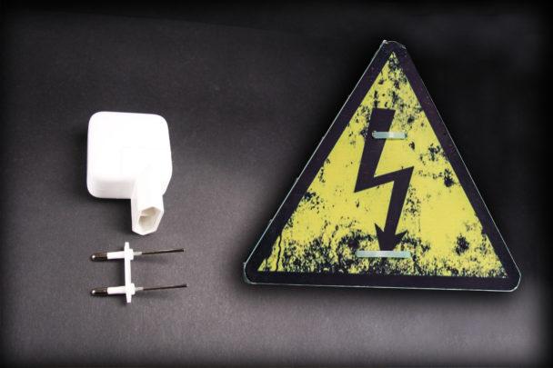 En trasig stickpropp invid en varningsskylt för elfara