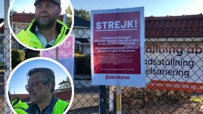 Skyltar med strejk-meddelanden på, med porträttbilder på två av strejkvakterna monterade invid sig.
