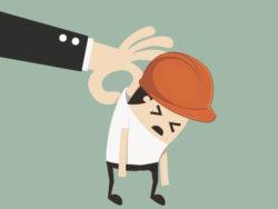 En tecknad person med bygghjälm och ledsen min blir bortlyft i kragen av en hand i kostym