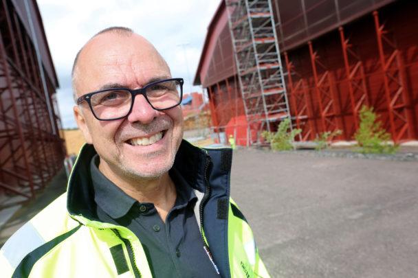 Per Magnusson framför en röd byggnad