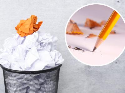 En full papperskorg med ett orange hopknölat papper högst upp. En bild av en penna är monterad i hörnet.
