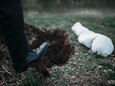 Foten på en person som gräver en grav med en spade. Bredvid gropen ligger ett långt vitt bylte