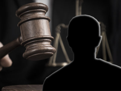 Silhuetten av en man monterad framför en domarklubba och en våg