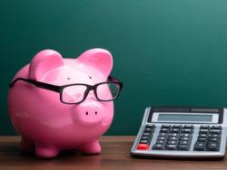En rosa spargris med stora glasögon,. bredvid en miniräknare