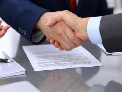 Två personer skakar hand över en samling papper på ett mötesbord