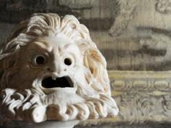 En grekisk antik skulptur av ett ilsket ansikte med svallande hår