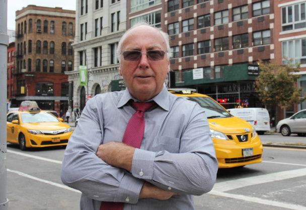 Chris Erikson står på ett övergångsställe med en stadsvy i bakgrunden, bland annat två gula taxibilar.