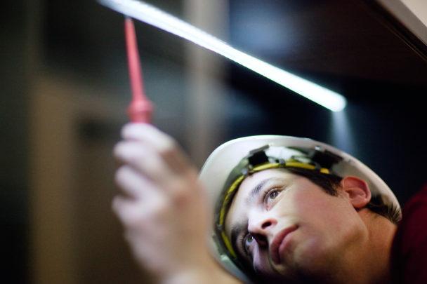 En ung person i skyddshjälm mäter spänning med ett verktyg