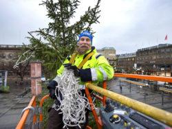 Patrik Jansson uppe i skyliften vid granens topp, hållandes en lång ljusslinga