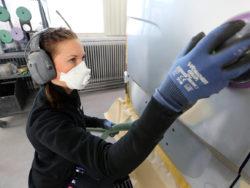 En lackerare i munskydd och hörselskydd, som arbetar på en bil