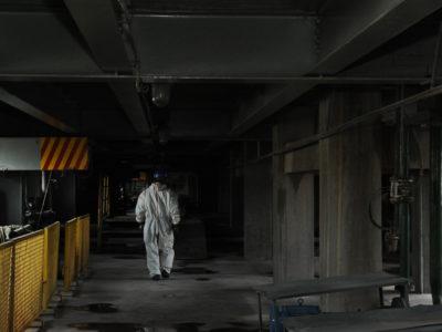 En arbetare i vit skyddsoverall går genom en källare