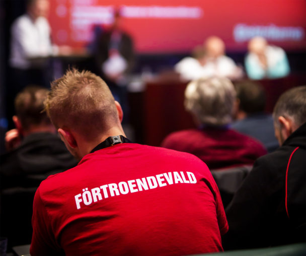 """Ryggtavlan på en person på ett möte. Personens tröja är röd och har ordet """"Förtroendevald"""" tryckt i vita bokstäver."""