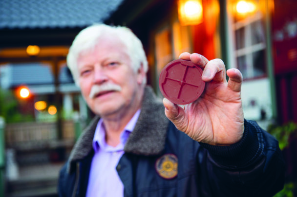 Sören Kling håller upp ett plastlock mot kameran