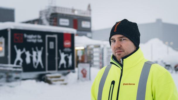 Mathias Hansson framför arbetarplatsens baracker utomhus i snön