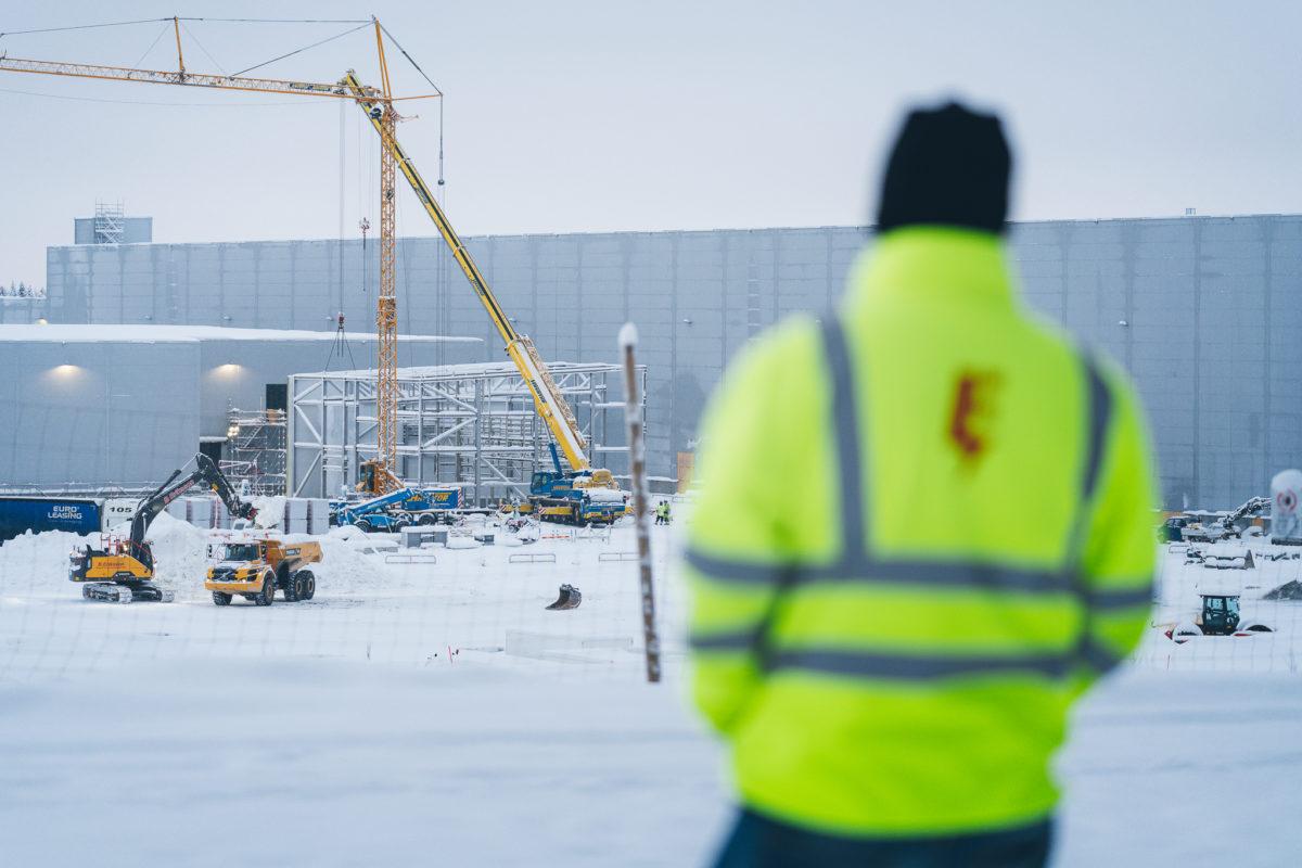 Mathias Hansson utomhus i snön, med arbetsplatsen i bakgrunden