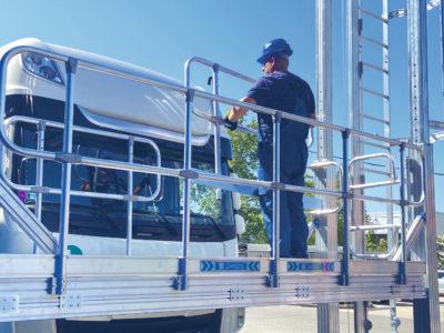 En person i bygghjälm på en plattform framför en lastbilsfront