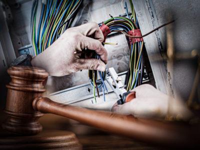 Två händer som klipper av kablar i ett elskåp, med en domarklubba i trä monterat över