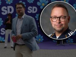 En bild på Jimmie Åkesson som håller tal framför en vägg med SD:s logga på, med ett foto på Jussi Jusola Nieminen monterat över