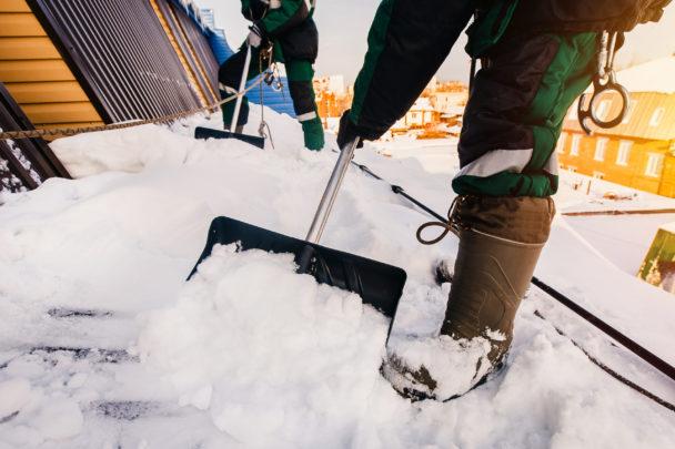 Benen på två personer som skottar snö från ett tak