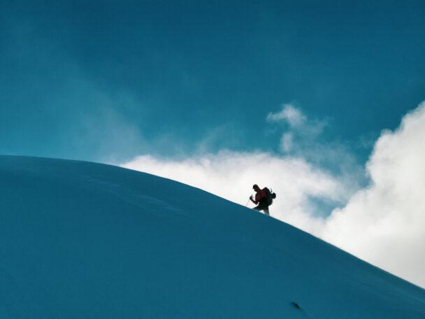 Silhuetten av en person som bestiger ett snöigt berg