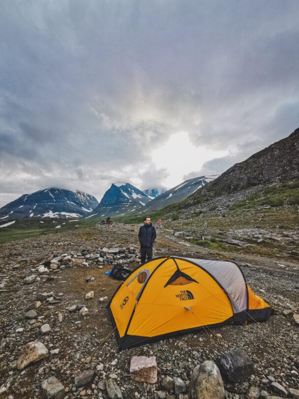 En person invid ett tält på en bergsplätt