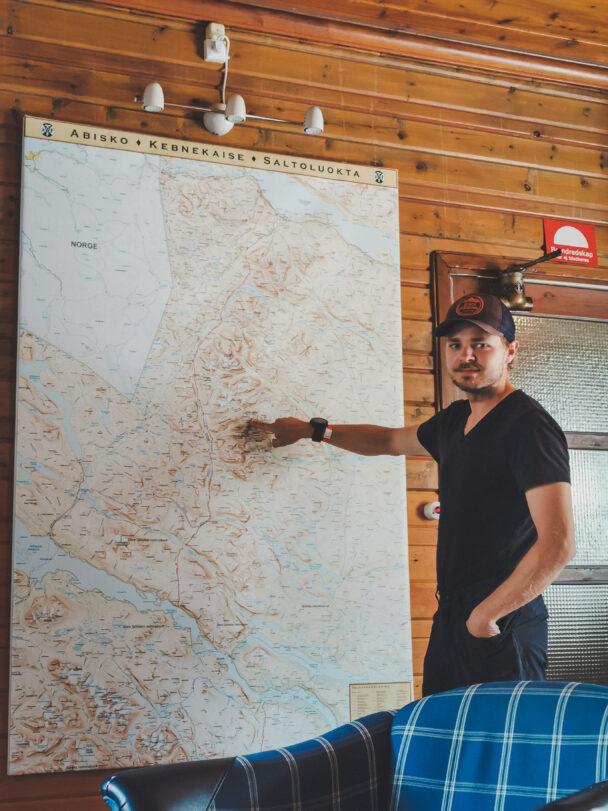 Anton Levein pekar på en stor karta i en stuga