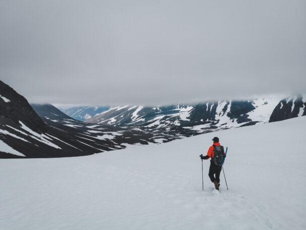 En person vandrar över en snöig slätt mot ett berg
